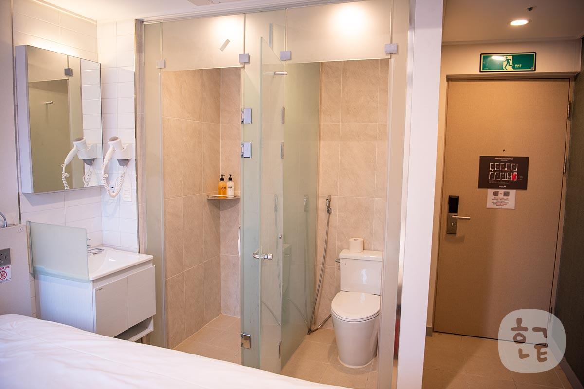 ソウルNホテルのダブルルームの内観写真 トイレとシャワールームと机